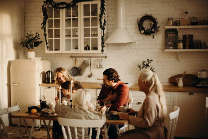 Družina sedi za mizo.