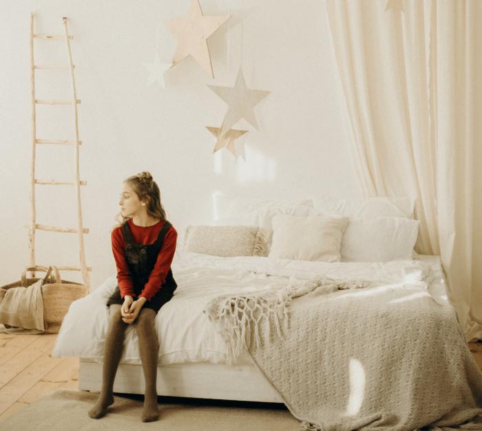 Deklica sedi na postelji.